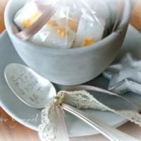 Betontasse gefüllt mit Zückerli und Silberlöffel