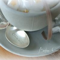Tasse gefüllt mit Zückerli und Silberlöffel